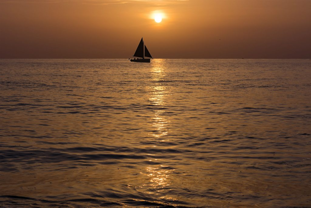 sail boat silhouette on the horizon just after sun set in naples